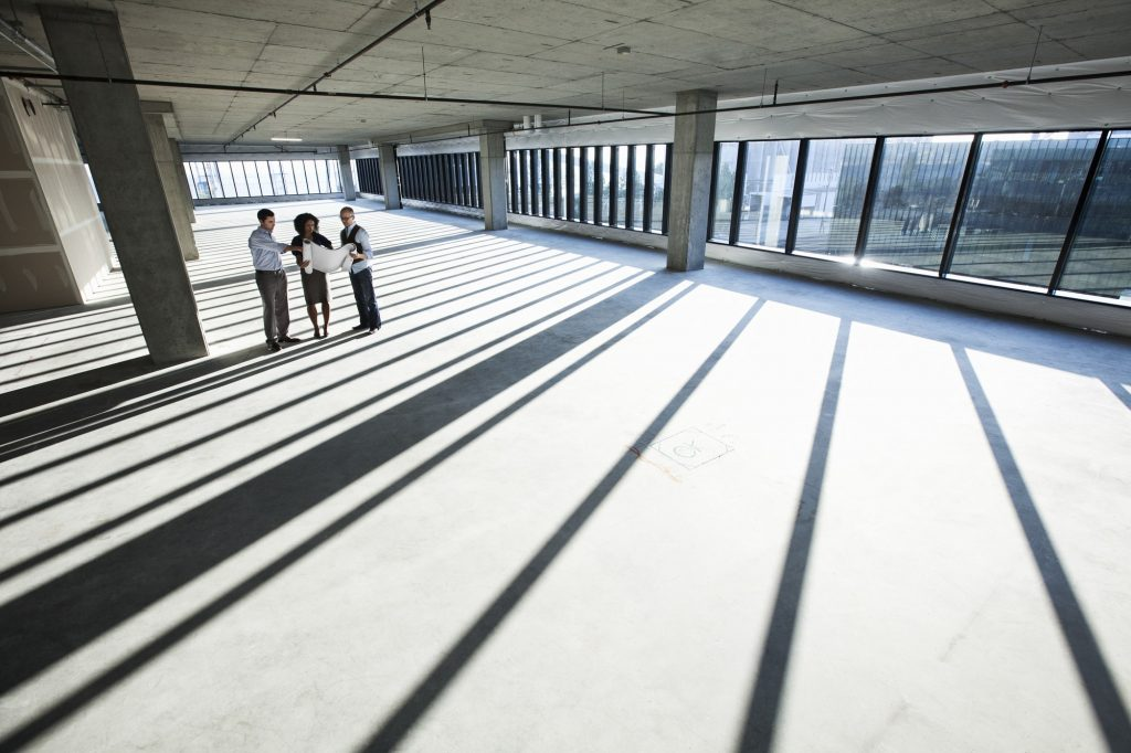 Mixed race team of business people touring a new empty raw office space.