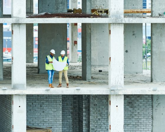 Two Builders Holding Construction Plans